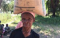 F. Maria Munenge 68, on her way home while carrying a bag of maize bought with money  she got from Save the Children.