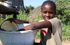 Nokwanda* 10, helps her grandmother wash dishes after their meal